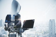 Invest and trade concept. Hacker in hoodie using laptop with forex chart grid on abstract city background. Invest and trade concept. Double exposure royalty free stock images