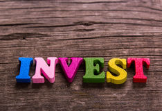 Invest word made of wooden letters. Invest word made from colored wooden letters on an old table. Concept Stock Image