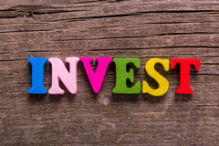 Invest word made of wooden letters Stock Photos