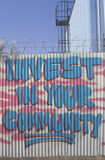 Invest in your community� statement painted on a fence during the Los Angeles riots Royalty Free Stock Images