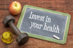 Invest in your health advice. Invest in your health - blackboard sign against weathered barn wood with a dumbbell, apple and tape measure stock image