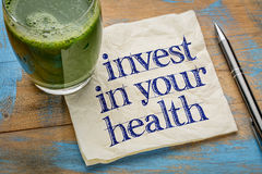 Invest in your health advice. Or reminder - handwriting on a napkin with a glass of fresh, green, vegetable juice Royalty Free Stock Photography