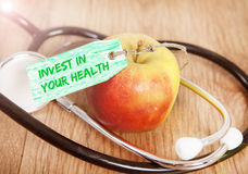 Invest in your health. An apple and a stethoscope with the text invest in your health Royalty Free Stock Photography