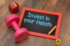 Invest in your Health concept with dumbbell and apple Stock Image