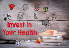 Invest in your health. Stack of books and a stethoscope on a wooden background Royalty Free Stock Images