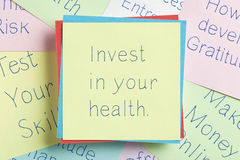 Invest in your health written on a note. Top view of Invest in your health handwritten on a note Royalty Free Stock Photo
