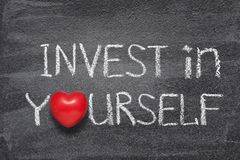 Invest in yourself. Phrase handwritten on chalkboard with red heart symbol instead of O stock photos