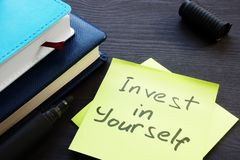 Invest in yourself. Memo sticks and note pad. Invest in yourself. Memo sticks and note pads stock photos