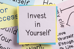 Invest in Yourself written on a note. Top view of Invest in Yourself handwritten on a note Royalty Free Stock Photography