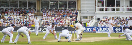 The Investec Ashes First Test Match Day Four. NOTTINGHAM, ENGLAND - July 13, 2013: Graeme Swann bowls the ball to Ed Cowan as the fielders crowd around during stock photo