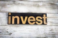 Investeer Letterzetselword op Houten Achtergrond royalty-vrije stock foto's