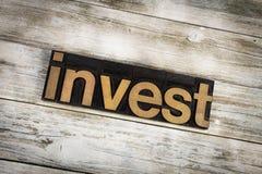 Investeer Letterzetselword op Houten Achtergrond royalty-vrije stock afbeelding