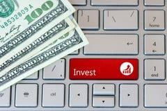 Investeer Rode Knoop op laptop toetsenbord met dollarbankbiljetten De mening van de close-up royalty-vrije stock afbeeldingen