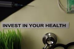 Investeer in Uw Gezondheid met inspiratie en gezondheidszorg/medisch concept op bureauachtergrond stock foto's