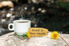 Investeer in uw gezondheidstekst met koffiekop stock foto