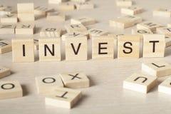 Investeer woord op houtsnede wordt geschreven die Stock Afbeelding