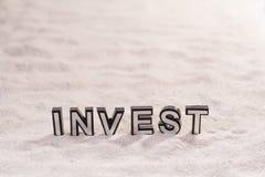 Investeer woord op wit zand royalty-vrije stock foto