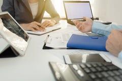 Investeerder de uitvoerende het bespreken gegevens van de plan financiële grafiek over bureaulijst met laptop en tablet Stock Foto