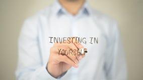 Investendo in voi stesso, scrittura dell'uomo sullo schermo trasparente Fotografia Stock