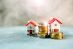 Investering i fastighet och stigning av begreppet för huspris Hus för liten modell med det röda taket som omges av mynt arkivbild