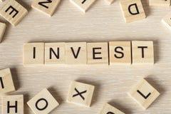 Investieren Sie das Wort, das auf hölzernen Block geschrieben wird Lizenzfreie Stockfotografie