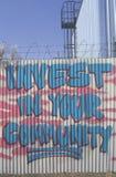 Investieren Sie in Ihrer community? Anweisung, die auf einem Zaun während der Los- Angelesaufstände gemalt wird lizenzfreie stockbilder