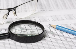 Investigação empresarial Close up dos espetáculos lupa e lápis no papel com dígitos imagens de stock