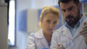 Investiga fórmulas químicas de dibujo sobre el vidrio almacen de video
