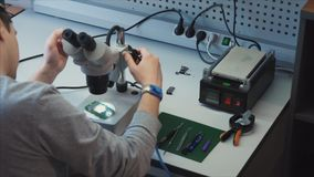 Investigación de la electrónica y organización de servicio El ingeniero puso el microscopio almacen de metraje de vídeo