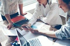 Investigación del nuevo producto Papeleo en la tabla, el ordenador portátil y el teléfono móvil Equipo de lanzamiento en oficina imagenes de archivo