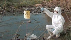 Investigación peligrosa del área, científicos del hazmat en la ropa protectora que recoge la muestra infectada de agua en los tub almacen de video