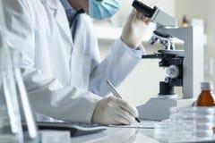 Investigación que conduce del científico con el microscopio foto de archivo