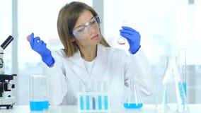 Investigación que hace ocupada y reacción del científico de sexo femenino en laboratorio almacen de metraje de vídeo