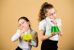 investigaci?n de la ciencia en laboratorio Conocimiento y educaci?n De nuevo a escuela peque?as muchachas elegantes con el frasco imágenes de archivo libres de regalías