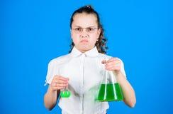 investigaci?n de la ciencia en laboratorio Peque?a colegiala Educaci?n y conocimiento pequeña muchacha con el frasco de prueba De foto de archivo