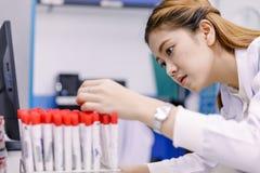 Investigador asiático joven que mira el frasco en el trabajo de la ciencia Imagen de archivo