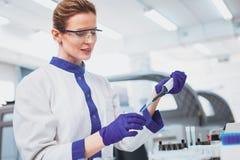 Investigador atento que hace el experimento químico Imagenes de archivo