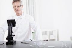 Investigador científico con el microscopio Imagen de archivo libre de regalías