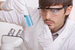 Investigador con el tubo líquido azul imagen de archivo libre de regalías