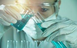 Investigador con los tubos de ensayo químicos del laboratorio de cristal con el líquido fotos de archivo libres de regalías