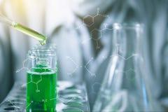 Investigador con los tubos de ensayo químicos del laboratorio de cristal con el líquido imagen de archivo libre de regalías