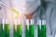 Investigador con los tubos de ensayo químicos del laboratorio de cristal con el líquido fotografía de archivo