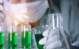 Investigador con los tubos de ensayo químicos del laboratorio de cristal con el líquido imagenes de archivo