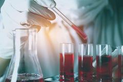 Investigador con los tubos de ensayo químicos del laboratorio de cristal con el líquido imágenes de archivo libres de regalías
