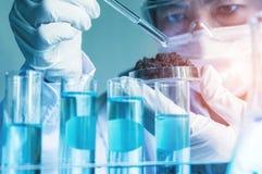 Investigador con los tubos de ensayo químicos del laboratorio de cristal con el líquido foto de archivo