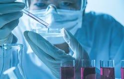 Investigador con los tubos de ensayo químicos del laboratorio de cristal con el líquido imagen de archivo