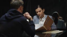 Investigador de sexo femenino que compara las declaraciones sospechadas con los documentos del fichero, desconfianza almacen de metraje de vídeo