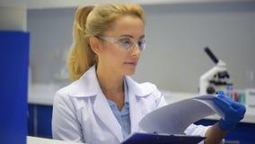 Investigador de sexo femenino que mira a través del documento el trabajo almacen de metraje de vídeo