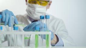 Investigador de sexo masculino con los tubos de ensayo en laboratorio almacen de video