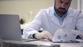 Investigador de sexo masculino serio que mecanografía en datos mientras que trabaja en el ordenador portátil almacen de video